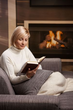 Woman sitting on sofa at home reading book, looking down. photo