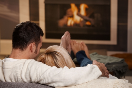 resting: Couple sitting on sofa at home in front of fireplace, rear view. Stock Photo