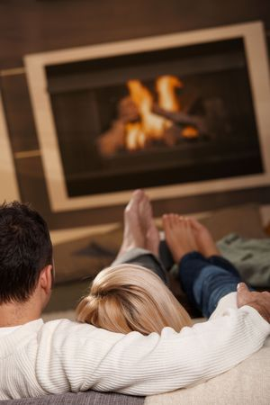 Couple sitting on sofa at home in front of fireplace, rear view. photo