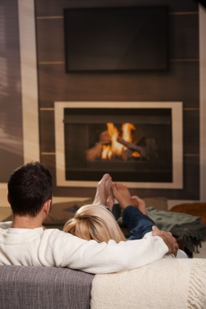 cosy: Couple sitting on sofa at home in front of fireplace, rear view. Stock Photo