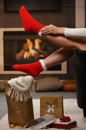 Female legs in santa claus socks at christmas in front of fireplace. Gifts on the floor. photo