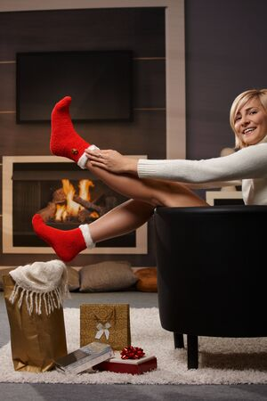 Woman preparing for Christmas, pulling on santa claus socks in front of fireplace. Gifts on the floor. photo