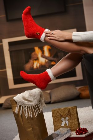 December: female legs in santa claus socks at christmas in front of fireplace. Gifts on the floor. photo