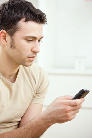 Young handsome man writting SMS on mobile phone. Stock Photo - 5851332