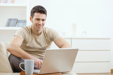 computer: Happy young man in t-shirt sitting on sofa at home, working on laptop computer, smiling. Stock Photo