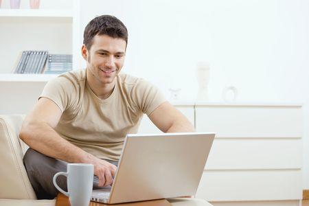 hombre sentado: Joven feliz en camiseta sentado en el sof� en casa, trabajando en un equipo port�til, sonriendo. Foto de archivo