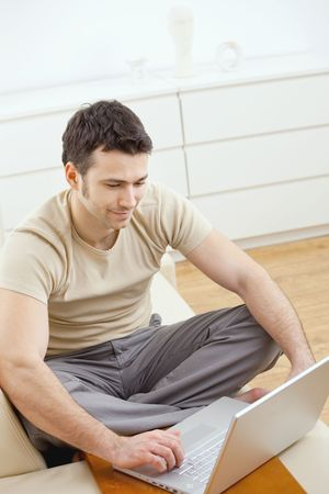 Happy young man in t-shirt sitting on sofa at home, working on laptop computer, smiling. Stock Photo - 5851330