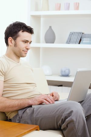 telework: Young man in t-shirt sitting on sofa at home, teleworking on laptop computer. Stock Photo