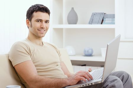 Happy young man in t-shirt sitting on sofa at home, working on laptop computer, smiling. photo