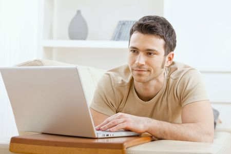 teleworking: Happy young man laying on sofa at home using laptop computer, smiling. Stock Photo