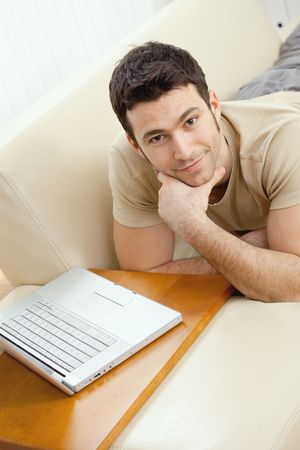 Happy young man laying on sofa at home using laptop computer, smiling. High-angle view. photo