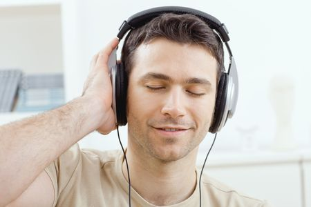 snug: Casual man listening music with headphones at home, relaxing with closed eyes, smiling. Stock Photo