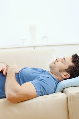 Young handsome man sleeping on couch at home, side view. Stock Photo - 5851280
