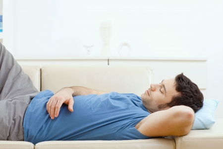 relaxed man: Young handsome man sleeping on couch at home, side view. Stock Photo