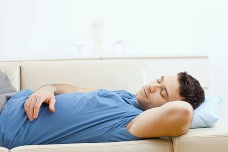 recline: Young handsome man sleeping on couch at home, side view. Stock Photo