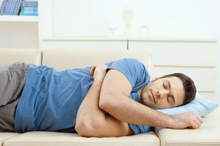 1 man only: Young handsome man sleeping on couch at home, side view. Stock Photo