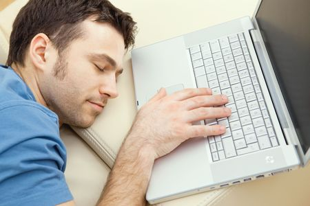 Man overslept by the keyboard of a laptop computer. eyes closed, high-angle view.   photo