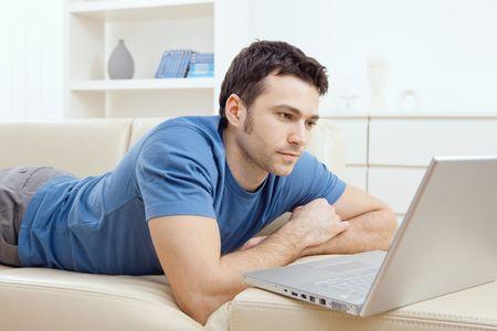 guy with laptop: Young man laying on sofa and using laptop at home. Stock Photo