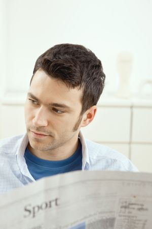 Handsome young man sitting on couch at home reading sport news in newspaper. Stock Photo - 5851270