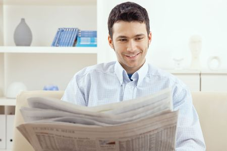 Happy young man sitting on couch reading newspaper at home, smiling. photo