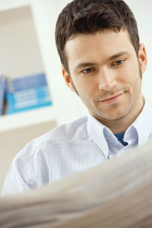 Handsome young man reading newspaper at home. Stock Photo - 5851175