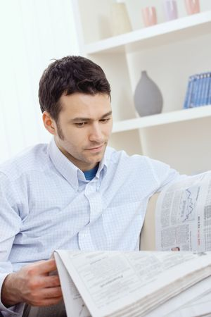 Handsome young man reading newspaper. Stock Photo - 5851263