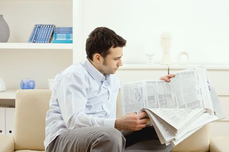 open collar: Handsome young man reading newspaper. Stock Photo