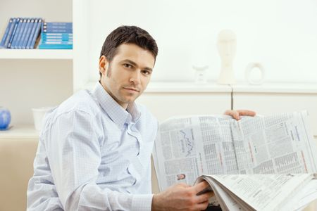 Casual young businessman reading business news, sitting on couch at home, looking at camera, smiling. Stock Photo - 5851169
