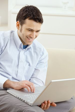mail man: Happy young man sitting on couch and working on laptop computer at home, smiling. Stock Photo