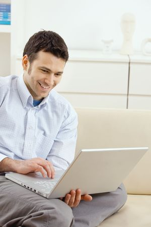 telecommuting: Happy young man sitting on couch and working on laptop computer at home, smiling. Stock Photo
