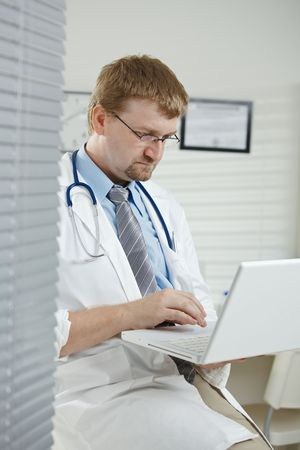 Medical office - male doctor sitting on desk holding laptop computer in hand, typing. Stock Photo - 5854629