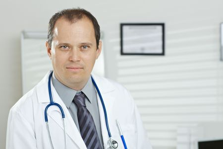 exam room: Medical office - portrait of middle-aged male doctor looking at camera.