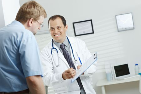 gratified: Medical office - smiling male doctor telling good news, explaining diagnosis on clipboard to happy patient.
