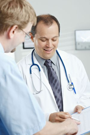 gratified: Medical office - smiling male doctor telling good news, showing negative test results to happy patient.
