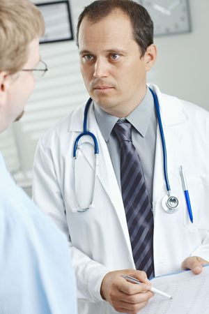 Medical office - middle-aged male doctor showing test results to patient. photo