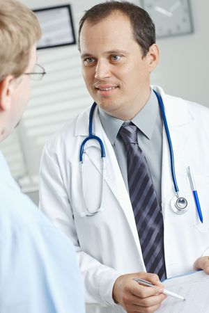 Medical office - smiling male doctor telling good news, showing negative test results to patient. photo