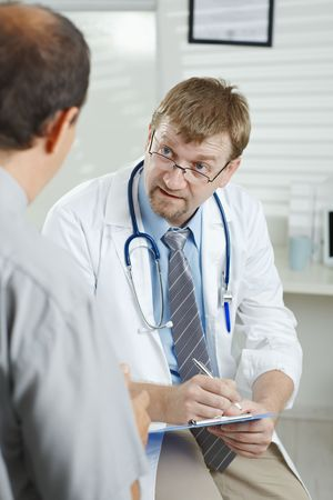 serious doctor: Medical office - Patient telling H1N1 flu symptoms to listening doctor.