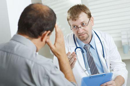 male headache: Consultorio m�dico - paciente con dolor de cabeza, dici�ndole a los s�ntomas de la gripe a m�dico escucha. Foto de archivo