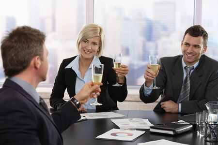 Happy young business people sitting around meeting table at office celebrating success with champagne, smiling. photo