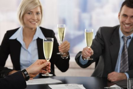 Happy young business people sitting around meeting table at office raising toast with champagne, smiling. Focus placed on hand in front. photo