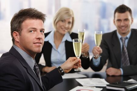 Happy middle-aged businessman sitting at meeting table at office celebrating success with champagne, smiling. photo