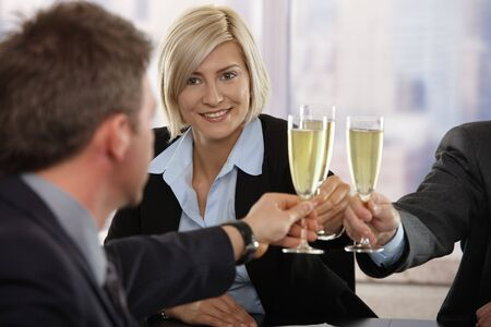 team winner: Happy young businesswoman celebrating success with champagne at office, smiling.