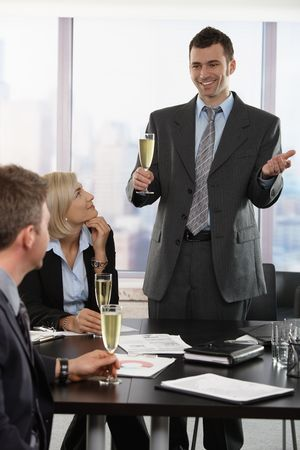 Businessman raising toast with champagne flutes, smiling. photo
