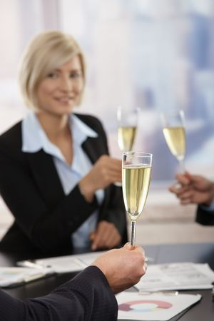 Business people raising toast with champagne flutes over meeting table at office. Focus placed on hand in front. photo