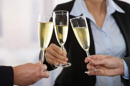 Close-up of hands: husiness people raising toast with champagne focus placed on flutes. photo