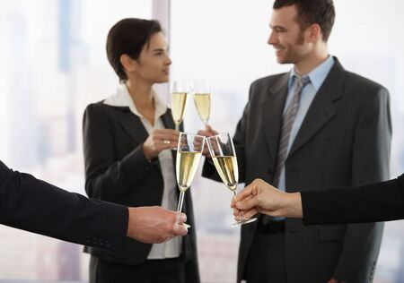 Business people raising toast with champagne at office, focus placed on flutes. photo