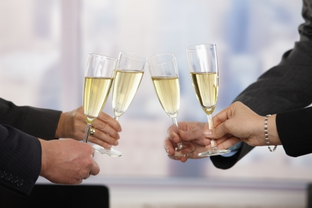 raising hands: Close-up of hands: business people raising toast with champagne focus placed on flutes.
