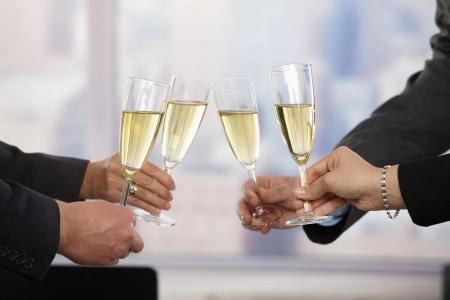 Gros plan des mains: des gens d'affaires levant des toasts avec un accent de champagne placés sur des flûtes. Banque d'images