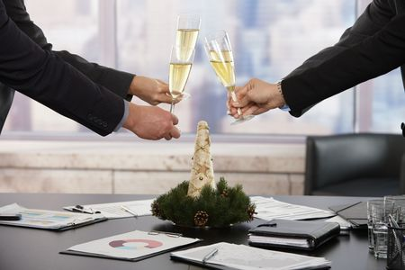 business event: Business people raising toast over meeting table with Christmas decoration at office. Focus placed on flutes in front.