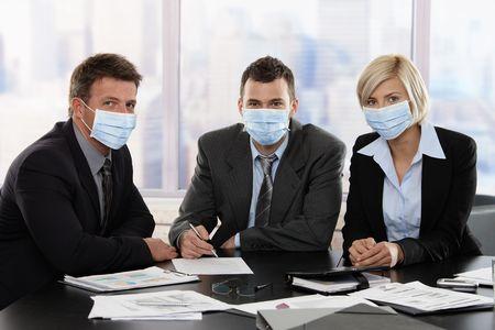 flu virus: Gente de negocios, temiendo la m�scara de protecci�n para la cara vistiendo de virus de la gripe porcina de h1n1 durante la reuni�n en la Oficina.